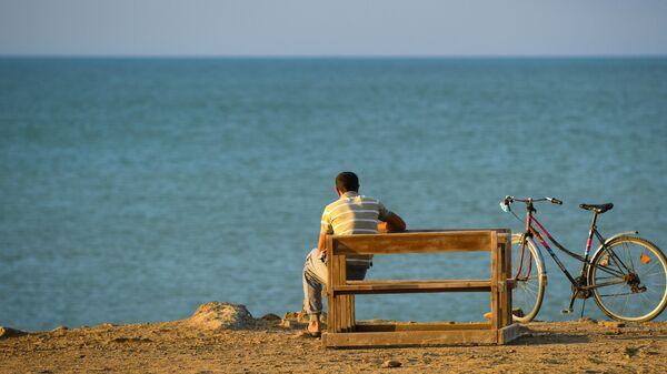Мужчина отдыхает на пляже в поселке Бузовна в Азербайджане