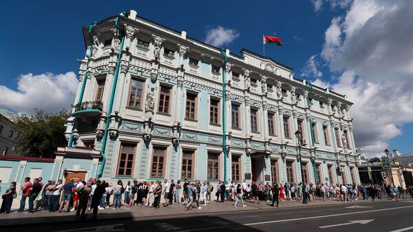 Люди стоят в очереди у здания посольства Белорусии в Москве во время голосования на выборах президента Белоруссии