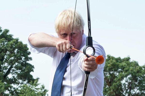 Премьер-министр Великобритании Борис Джонсон принимает участие в стрельбе из лука во время посещения летнего лагеря в Лондоне