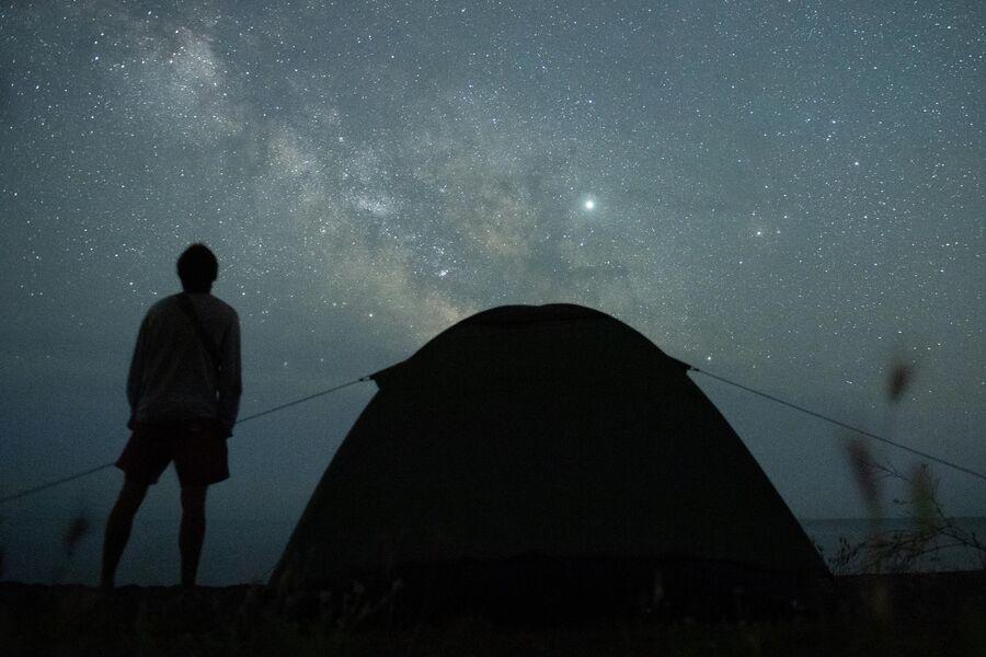 Мужчина наблюдает за звездным небом на берегу Черного моря возле поселка Морское в Крыму