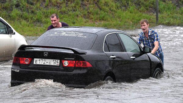 Мужчины выталкивают заглохший на дороге автомобиль во время ливня