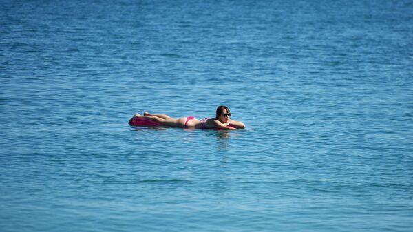 Девушка в море на надувном матрасе