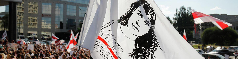 Люди держат флаг с портретом Светланы Тихановской в Минске