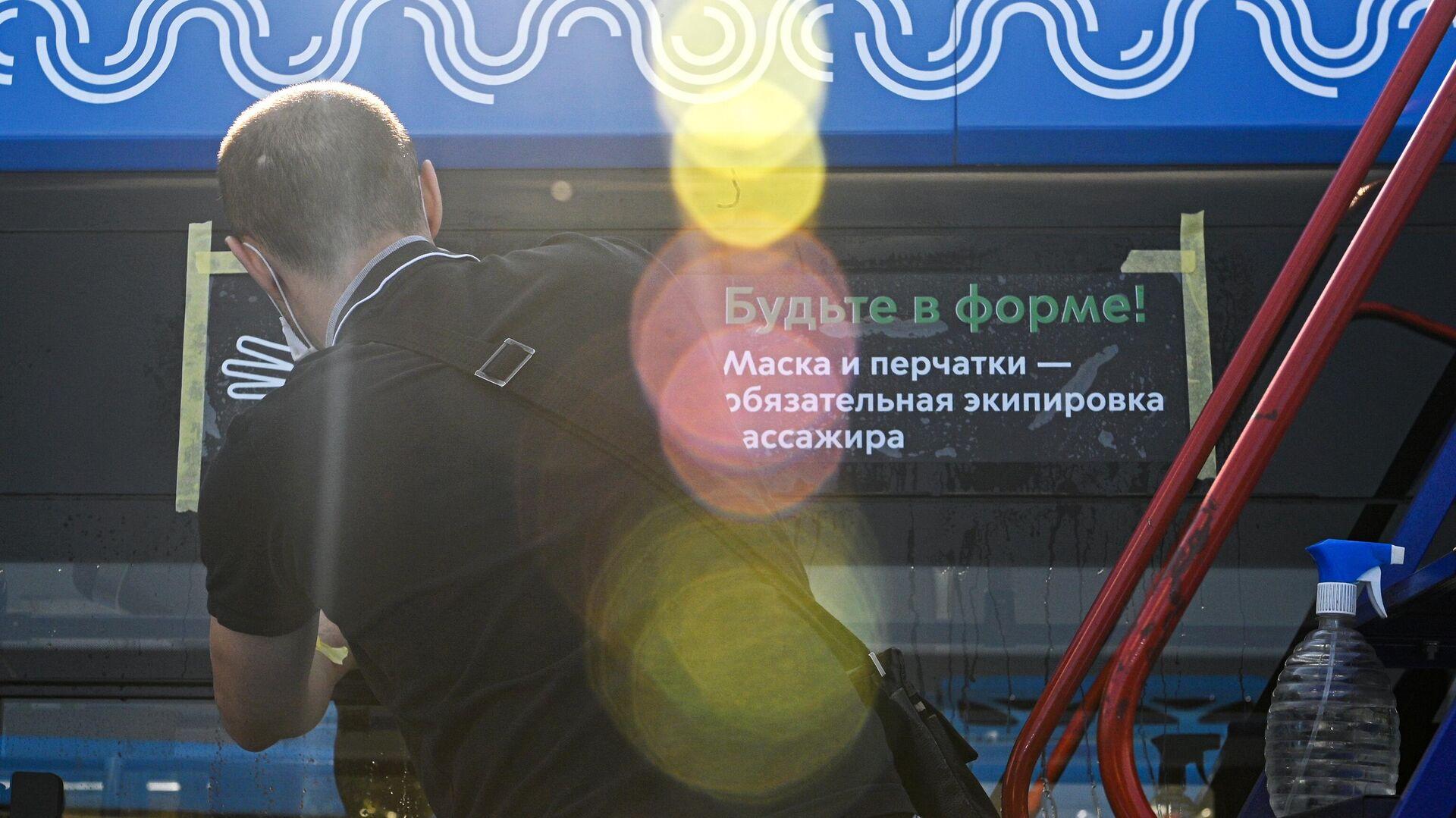 Размещение наклейки на электробусе, напоминающей о необходимости носить маски и перчатки в транспорте Москвы - РИА Новости, 1920, 02.10.2020