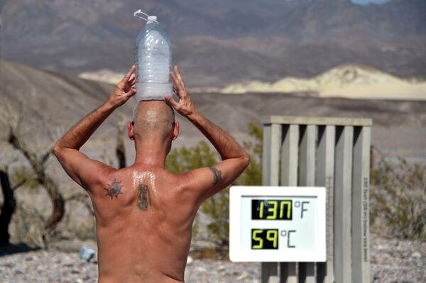 Мужчина с бутылкой льда на голове во время жары в Долине Смерти, Калифорния, США