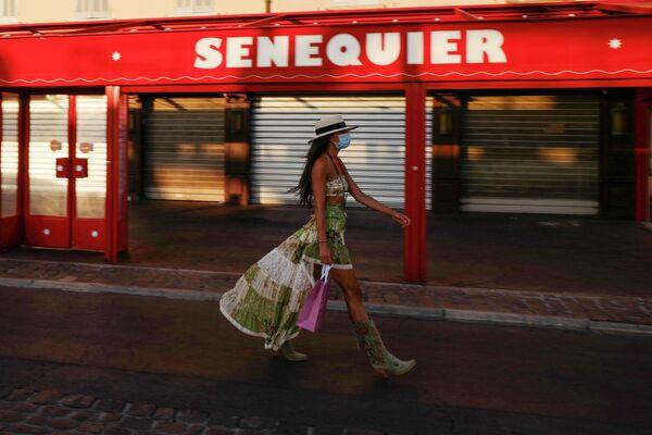 Женщина в защитной маске идет мимо закрытого кафе Le Cafe Senequier в Сен-Тропе