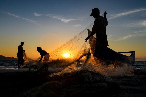 Рыбаки очищают сети после рыбалки в Банда-Ачех