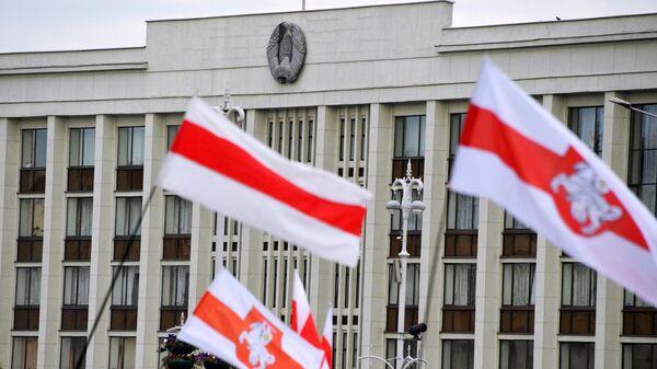 Флаги участников акции протеста на фоне Дома правительства на площади Независимости в Минске