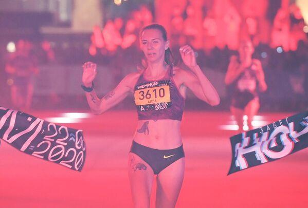 Участница финиширует в Ночном забеге 2020 в Москве
