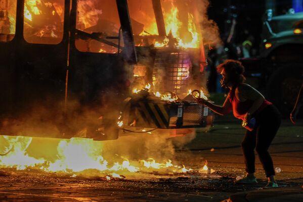 Протестующий возле горящего мусоровоза во время протестов в Кеноша, штат Висконсин