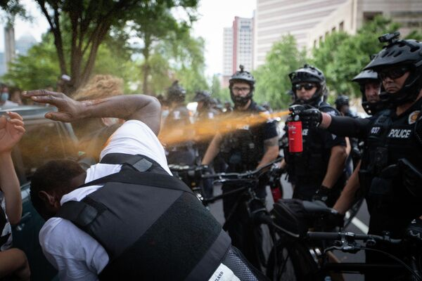 Сотрудник полиции распыляет на протестующих перцовый баллончик в Шарлотте, штат Северная Каролина