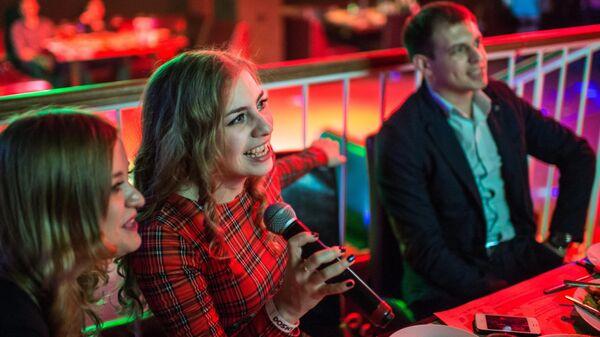 Молодые люди поют караоке в баре