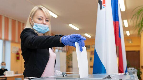 Женщина голосует на выборах губернатора Камчатского края на избирательном участке №51 в Петропавловске-Камчатском