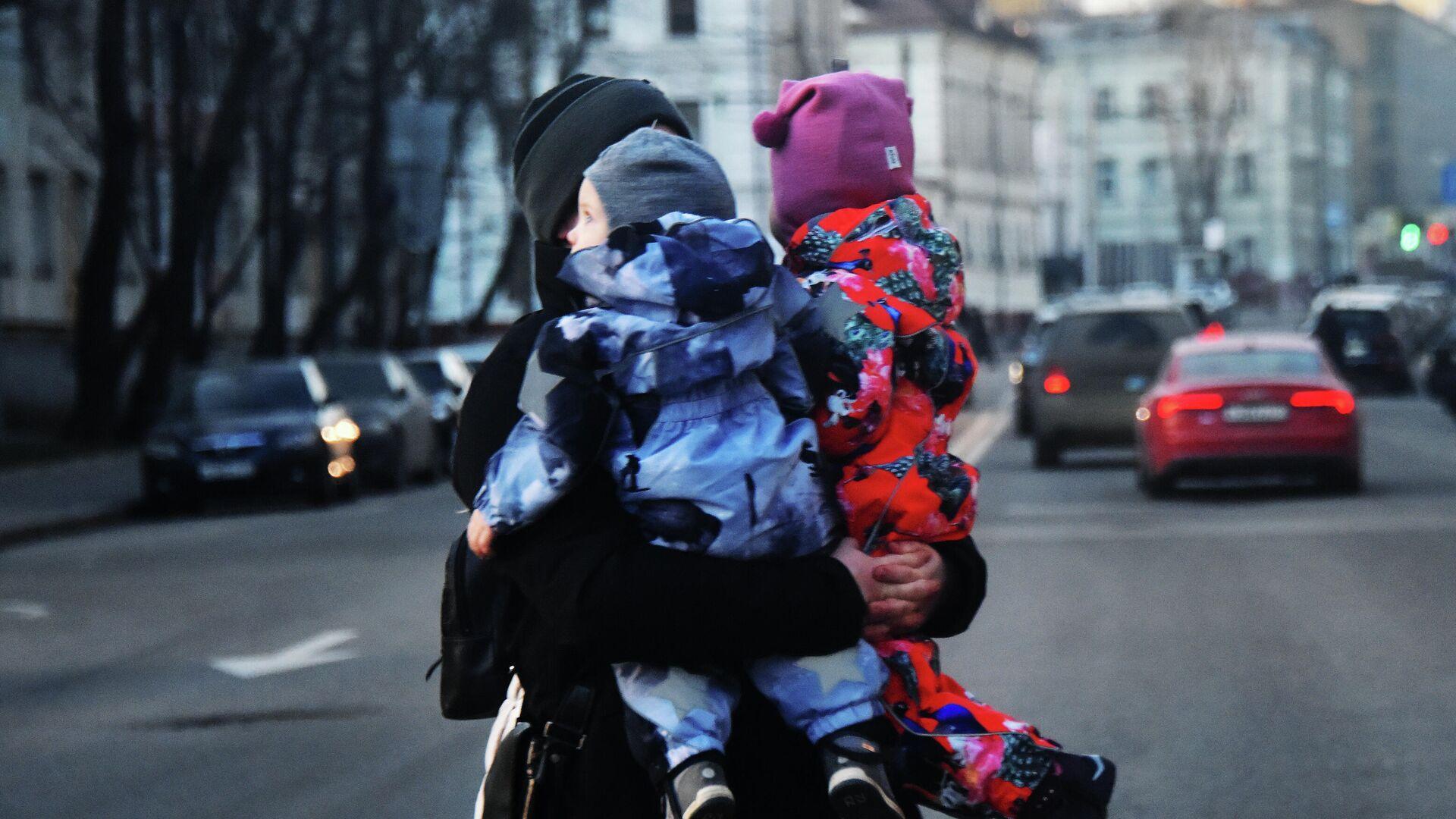 Женщина с двумя детьми на руках переходит дорогу. - РИА Новости, 1920, 15.09.2020