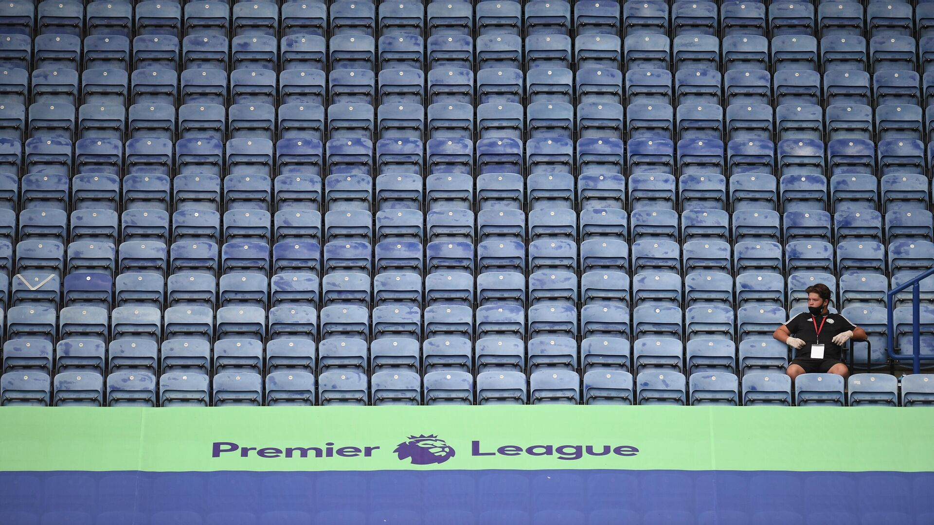 A member of staff sits in the empty stands during the English Premier League football match between Leicester City and Manchester United at King Power Stadium in Leicester, central England on July 26, 2020. (Photo by Oli SCARFF / POOL / AFP) / RESTRICTED TO EDITORIAL USE. No use with unauthorized audio, video, data, fixture lists, club/league logos or 'live' services. Online in-match use limited to 120 images. An additional 40 images may be used in extra time. No video emulation. Social media in-match use limited to 120 images. An additional 40 images may be used in extra time. No use in betting publications, games or single club/league/player publications. /  - РИА Новости, 1920, 16.09.2020