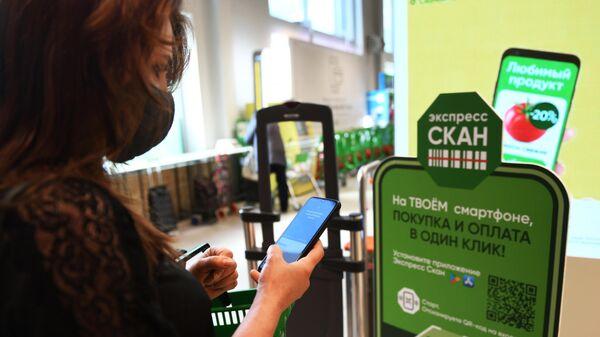 Девушка устанавливает мобильное приложение на смартфон, с помощью которого можно совершать бесконтактную оплату покупок