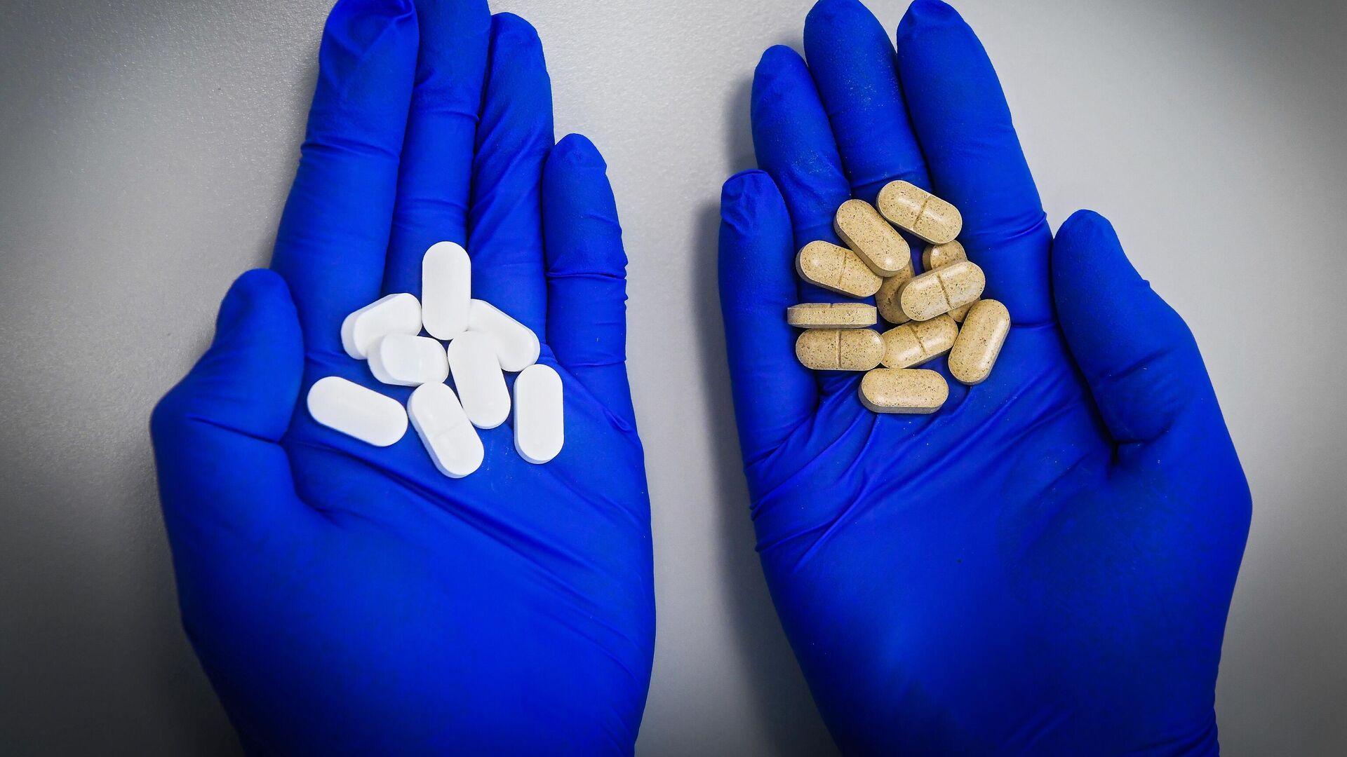 Сотрудник держит в ладонях лекарственные препараты - РИА Новости, 1920, 13.01.2021