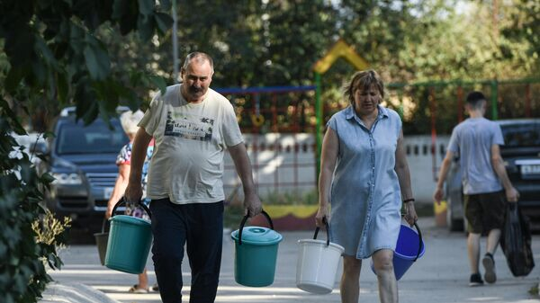 Жители Cимферополя идут чтобы набрать в емкости питьевую воду, привезенную в цистернах