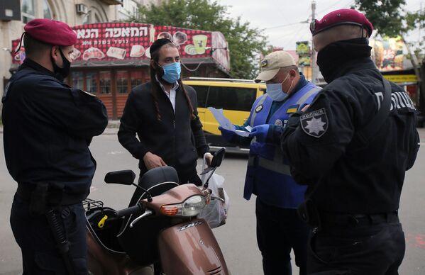 Сотрудники полиции города Умани проверяют документы паломника-хасида, прибывшего в город на празднование иудейского Нового года (Рош ха-Шана)