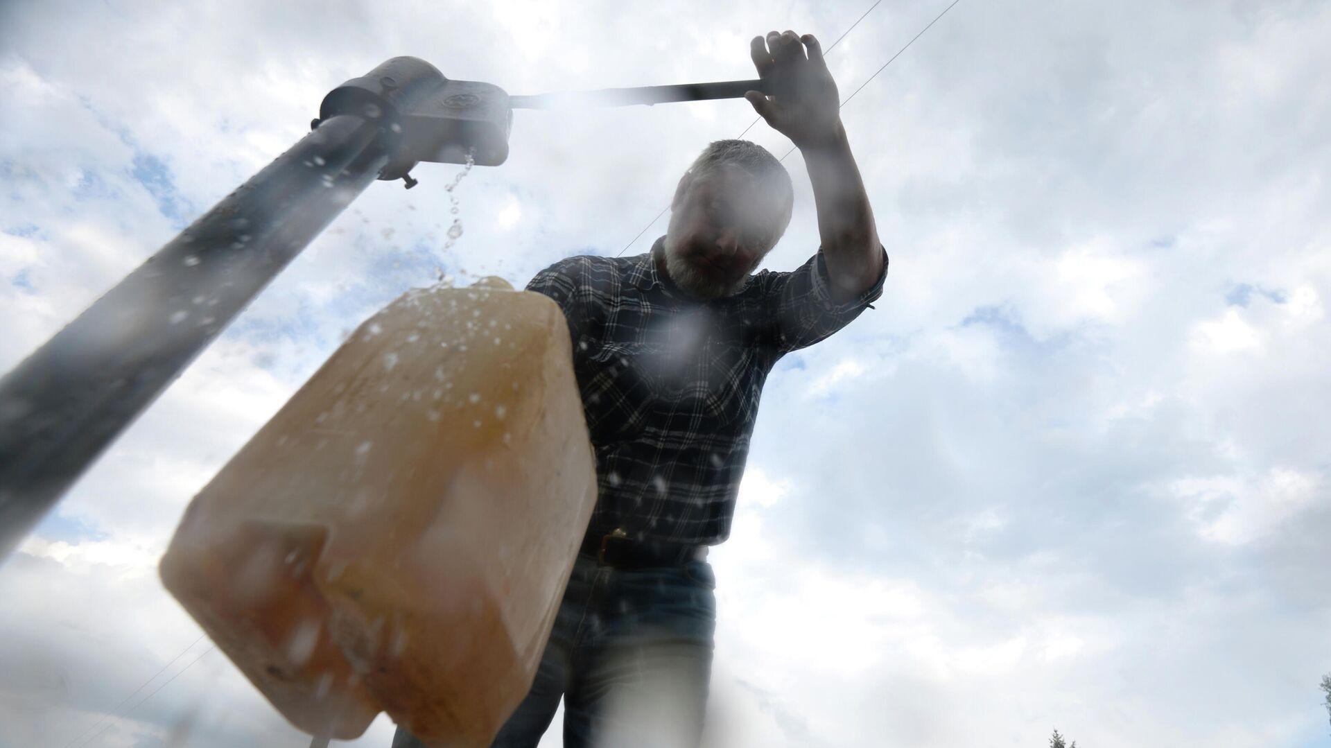 Мужчина набирает воду из колонки - РИА Новости, 1920, 01.08.2021