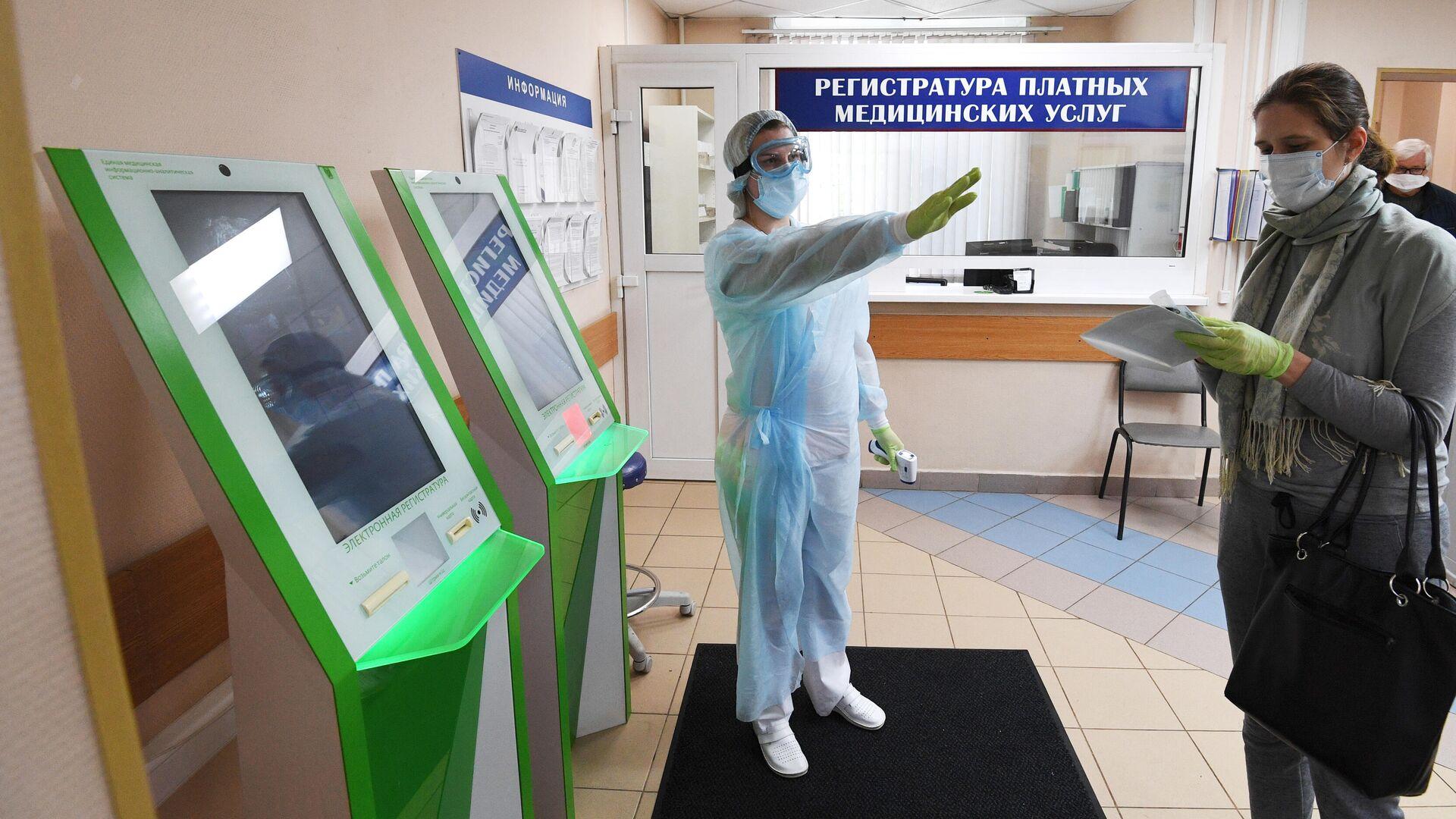 Посетитель и медработник в городской поликлинике № 209 в Москве - РИА Новости, 1920, 02.07.2021