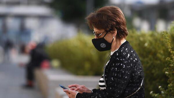Женщина в защитной маске у станции метро Парк культуры в Москве