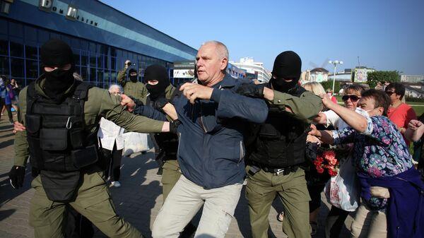 Сотрудники правоохранительных органов задерживают мужчину у во время митинга оппозиции в Минске