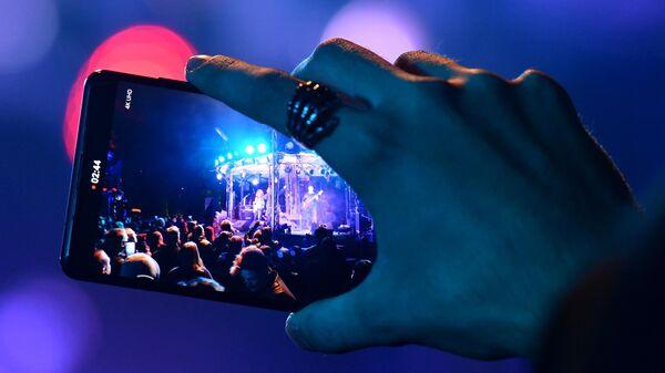 Зритель снимает на мобильный телефон выступление музыкантов на концерте