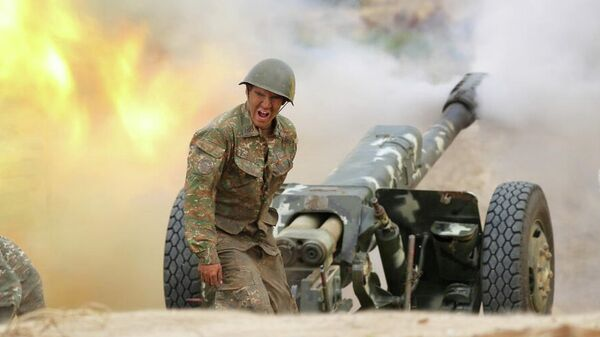 Военнослужащий стреляет из артиллерийского орудия во время боя с азербайджанскими силами в Нагорном Карабахе