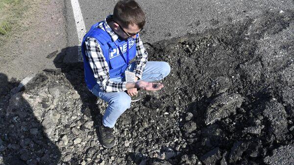 Журналист держит в руках осколок от снаряда в Мартакертском районе Нагорного Карабаха