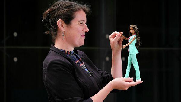 Доктор Сара Герсон, старший преподаватель Центра человеческого развития Кардиффского университета,  с куклой Барби в руках объявляет о результатах нового исследования