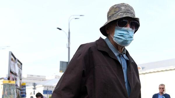 Мужчина в медицинской маске у станции метро Парк культуры в Москве
