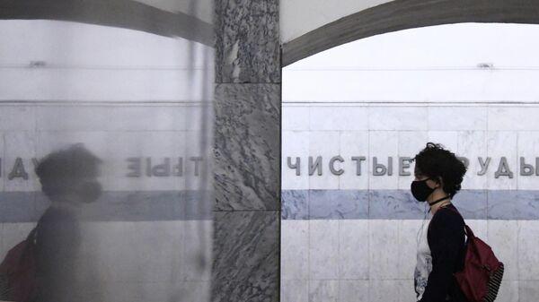 Девушка в маске в вестибюле станции метро Чистые пруды в Москве