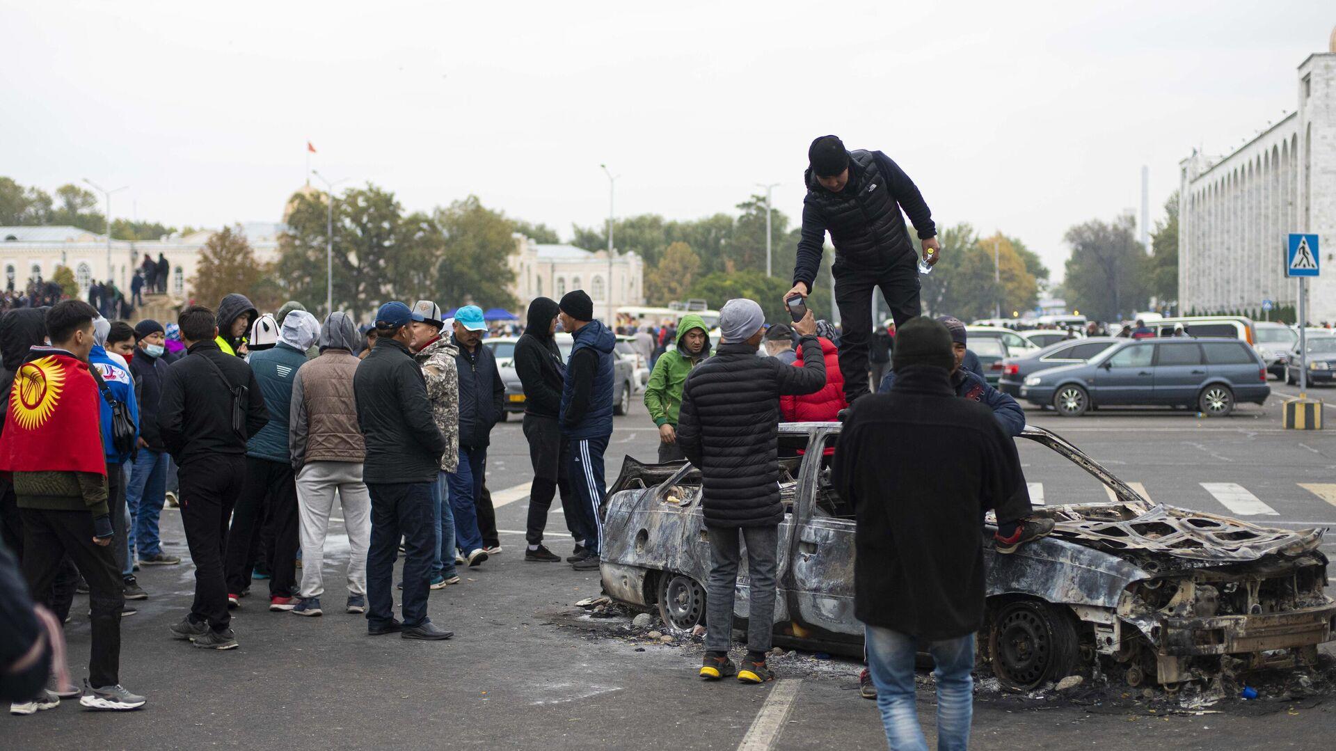 Протестующие у сожженного автомобиля на центральной площади Бишкека Ала-Тоо - РИА Новости, 1920, 06.10.2020