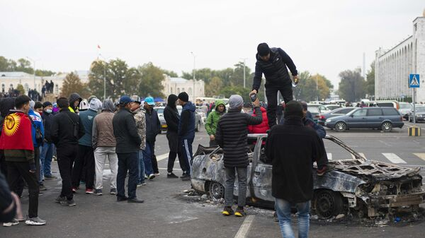 Протестующие у сожженного автомобиля на центральной площади Бишкека Ала-Тоо