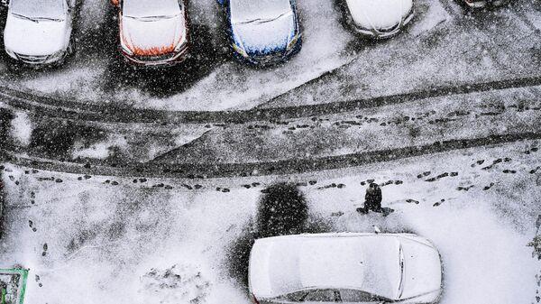 Прохожий на одной из улиц в Новосибирске во время первого снегопада