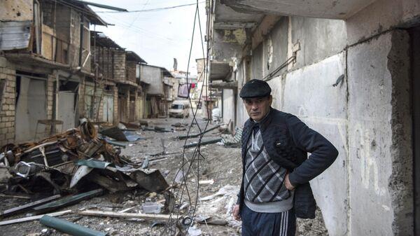 Мужчина на разрушенной улице города Степанакерт, который подвергся обстрелу