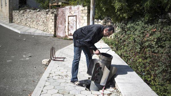 Местный житель у не разорвавшегося снаряда на улице города Мартуни