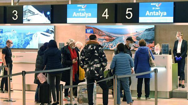Пассажиры во время регистрации на международный рейс в турецкий город Анталья в аэропорту Красноярска