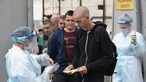 Сотрудники медслужбы раздают защитные маски и перчатки призывникам на входе в сборный пункт военного комиссариата Севастополя