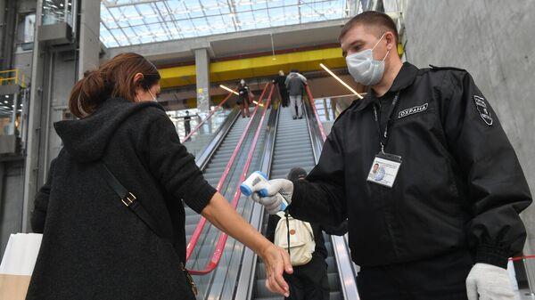 Сотрудник ТЦ Европолис измеряет температуру у посетителя торгового центра