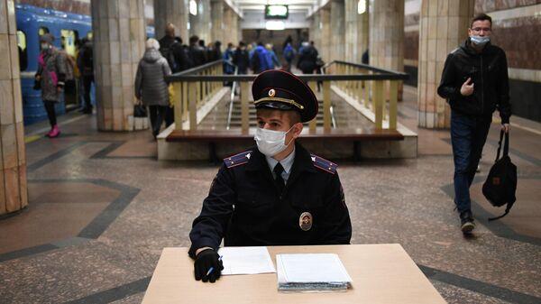 Сотрудник полиции в защитной маске на станции метро Красный проспект в Новосибирске