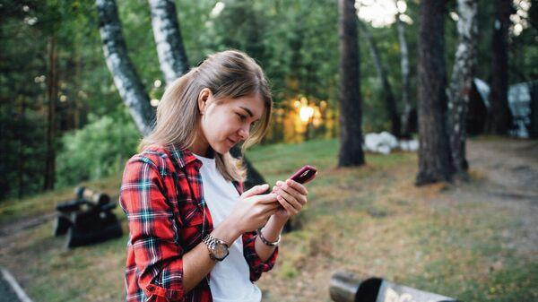 Девушка с мобильным телефоном во время похода