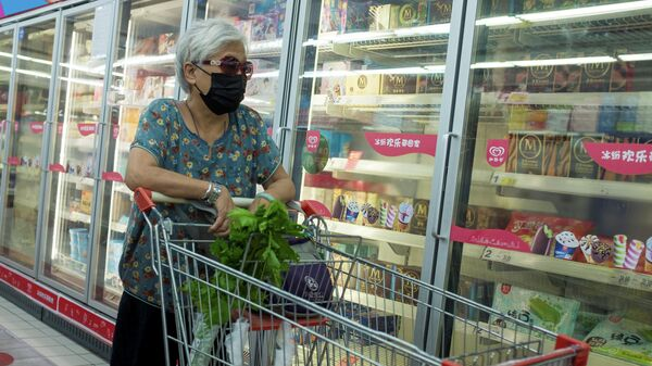 Женщина у стеллажа с замороженной продукцией в супермаркете в Пекине, КНР