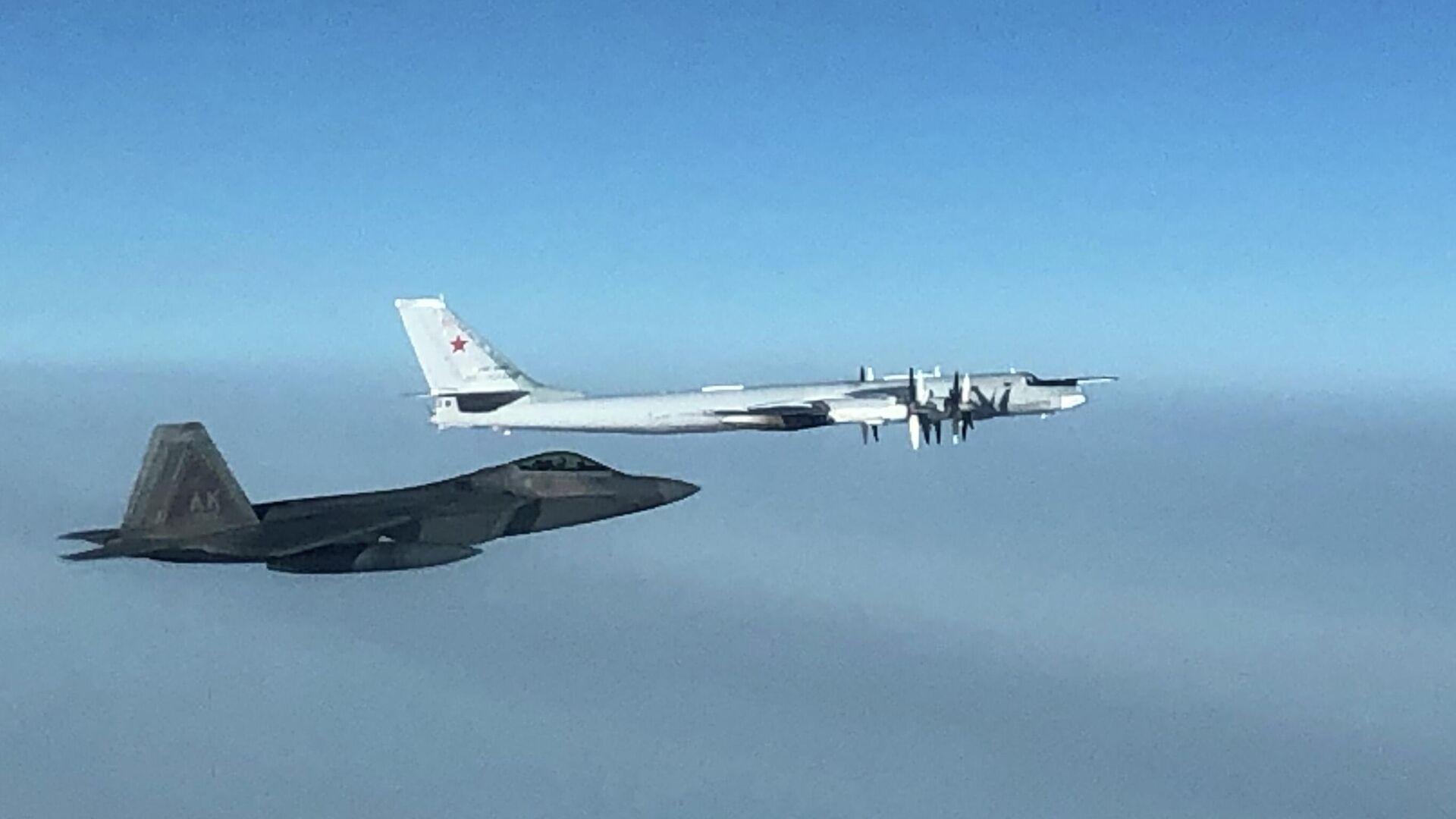 Истребитель F-22 командования воздушно-космической обороны США и российский бомбардировщик Ту-95 в небе у берегов Аляски - РИА Новости, 1920, 20.10.2020
