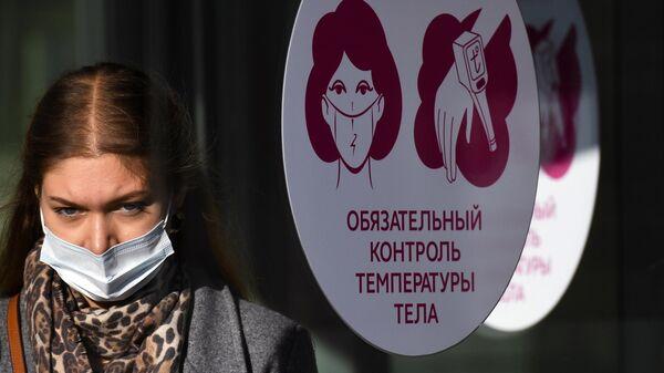 Девушка около входа в торговый центр на улице Гоголя в Новосибирске