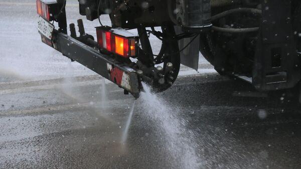Снегоуборочная машина обрабатывает улицу противогололедным (ПГМ) средством в Москве