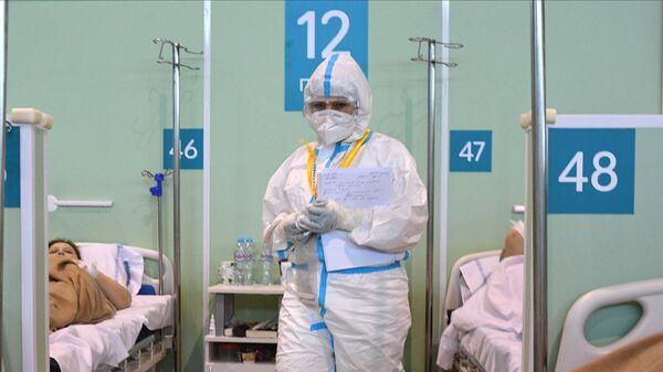 Медицинский работник и пациенты в палате временного госпиталя COVID-19 на ВДНХ в Москве
