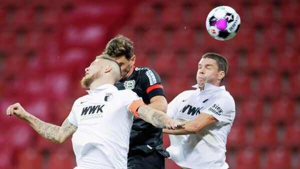 Leverkusen's Italian forward Lucas Alario (M), Augsburg's Dutch defender Jeffrey Gouweleeuw (L) and Augsburg's German defender Raphael Framberger vie for the ball during the German first division Bundesliga football match Bayer 04 Leverkusen v FC Augsburg, in Leverkusen, western Germany, on October 26, 2020. (Photo by Rolf Vennenbernd / POOL / AFP) / DFL REGULATIONS PROHIBIT ANY USE OF PHOTOGRAPHS AS IMAGE SEQUENCES AND/OR QUASI-VIDEO