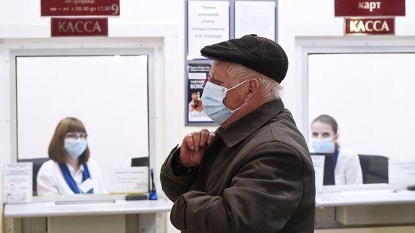 Пожилой мужчина в офисе управляющей компании в Новосибирске оплачивает услуги ЖКХ